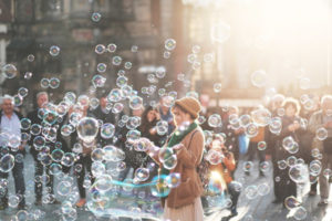 A person surrounded by people, sharing the experience of many floating bubbles.