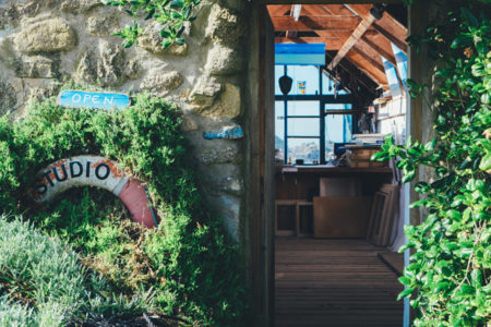 A working studio with open door surrounded by stone and plant life.
