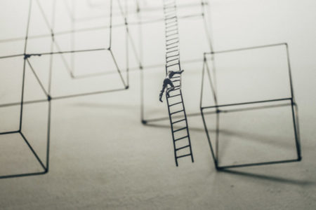 A figurine person climbing a long ladder with no foreseeable end.