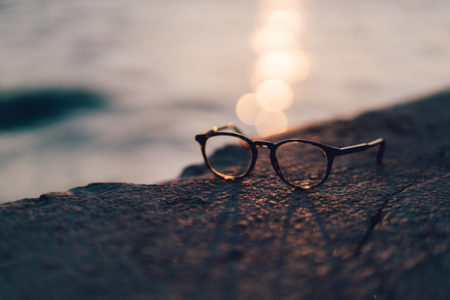 A pair of glasses with a sunset in the background.