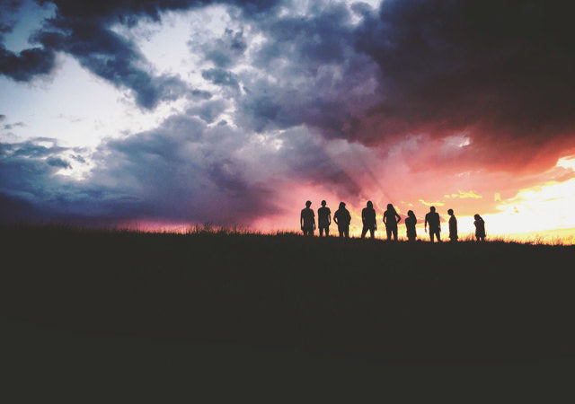 Silhouettes of people on a hill against a sunset.