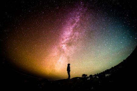 A person staring up at a great night sky full of stars.