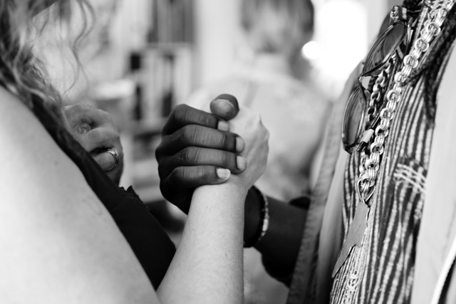 A white person and an African American person with their hands locked in unity.