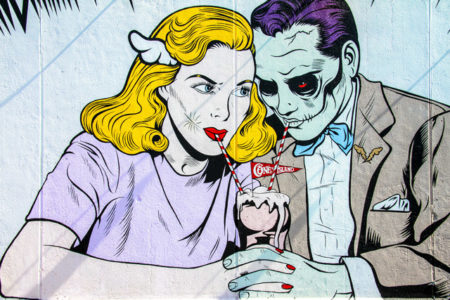 Graffiti of a woman sharing a milkshake with a zombie.