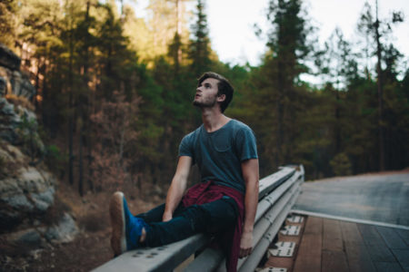 A man sitting on the side of the road, looking upwards.
