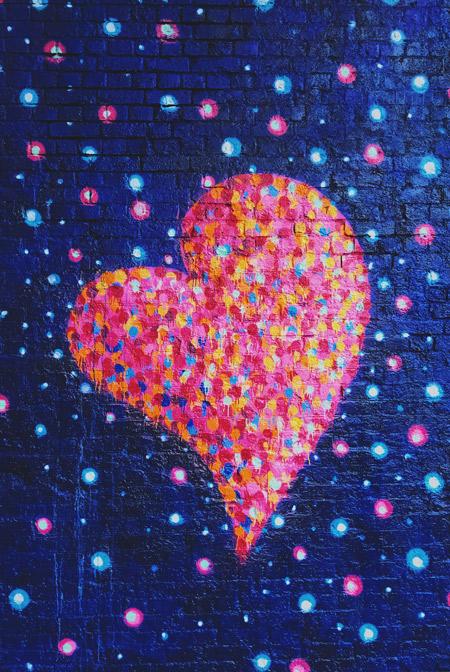 A large graffiti heart on a brick wall.