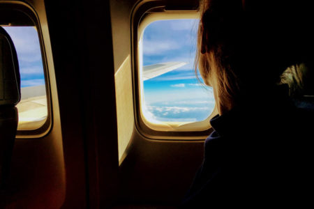 A woman looking out of an airplane window.