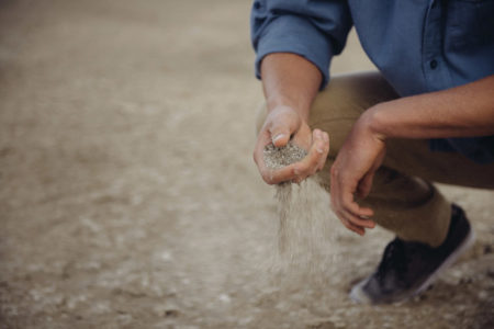 A man couched on the ground, with sand escaping from his hand.