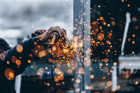 Sparks flying, as a worker polishes metal.