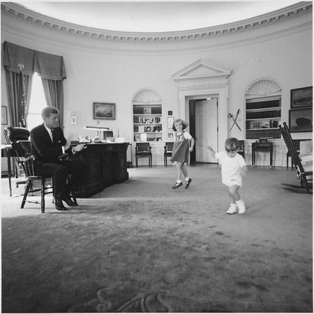 President Kennedy clapping as his children dance in the Oval Office.