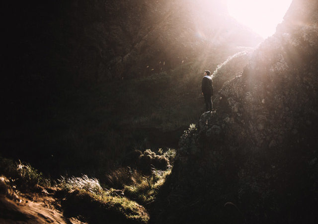A man in a shadowy valley, with the sun piercing from above.