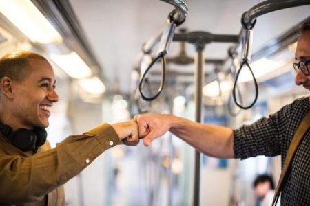 Two men fistbumping each other on a train.