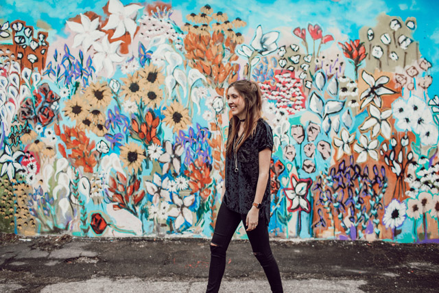 A woman smiling in front of a wall of graffiti flowers.