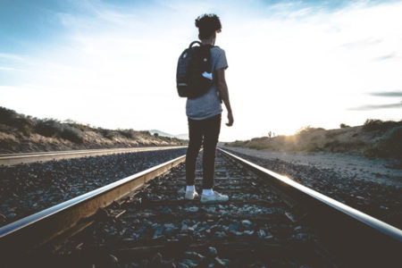 A man standing on train tracks looking to the sunrise.