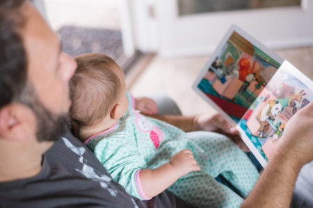 A father reading a picture book to his child.