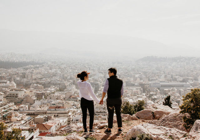 A couple standing on a hilltop overlooking a city.