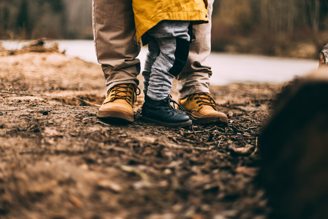 The boots of a parent and child.