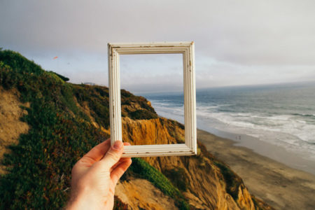 An empty frame held against an ocean landscape.
