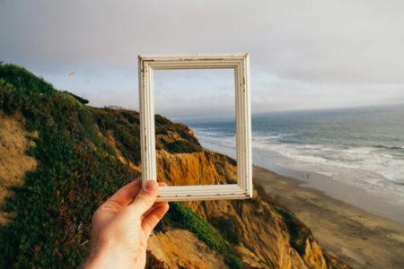 An empty frame held against an ocean landscape.
