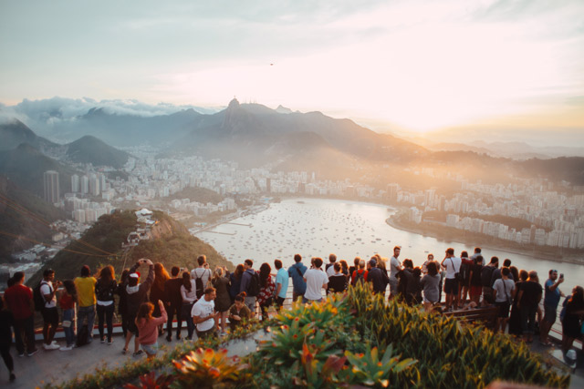 A crowd of diverse people overlooking a city by the sea.