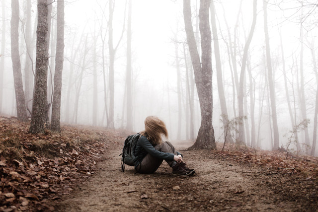 A woman sitting on the ground in the middle of a foggy forest.
