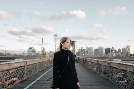 A woman looking thoughtfully at the cityscape.