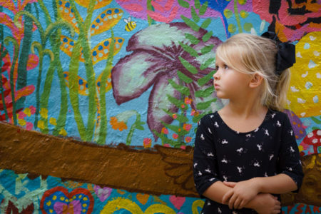 A little girl standing in front of a colorfully painted wall.