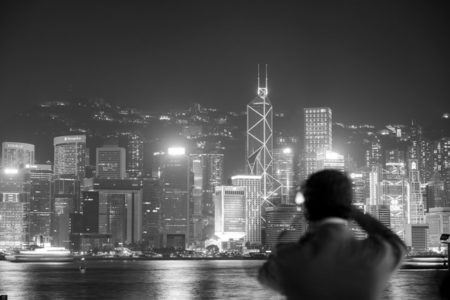 A man surveying the Hong Kong skyline at night.