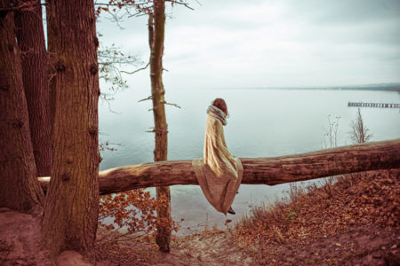 A woman sitting in solitude by a lake.