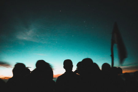 Silhouettes of people against a sunset.