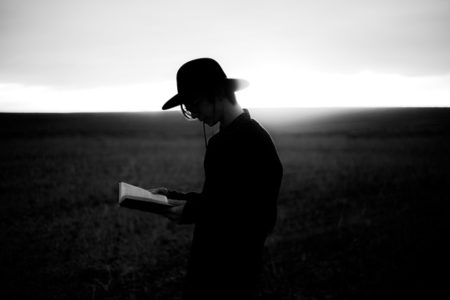 A man reading a book outside.