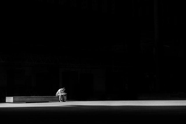 A man sitting on a bench, praying.