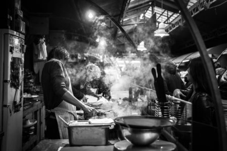 A man cooking in a public market.