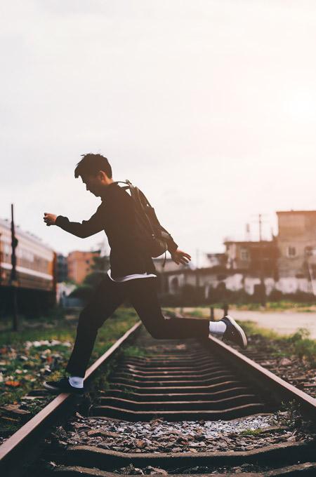 A man skipping across train tracks.