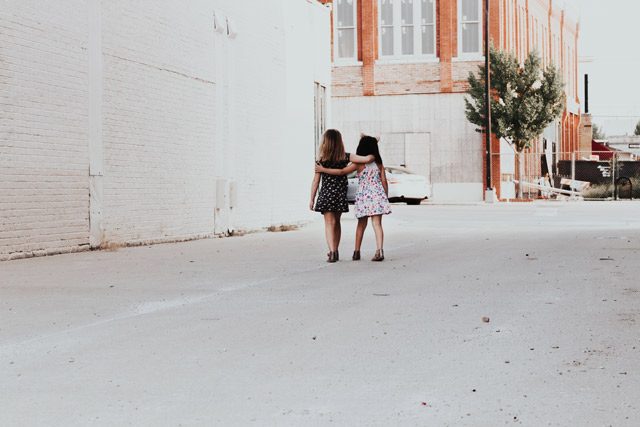 Two girls walking down the street.