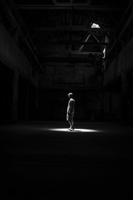 A man under a spotlight in a warehouse.