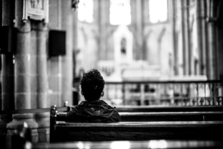 A person sitting in the pews of a large church.