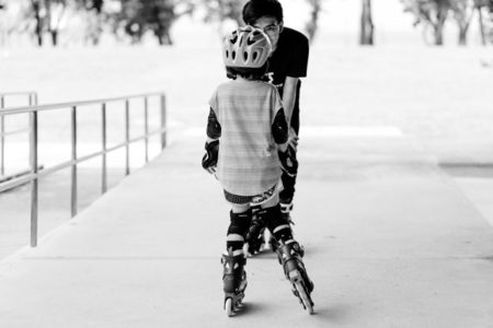 A kid learning to rollerblade.