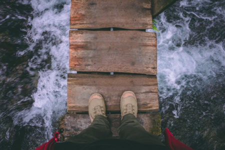 The view of someone's feet on a wooden bridge over water.