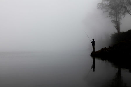 A man fishing in the fog.