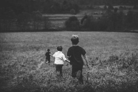 Three boys running in a field.
