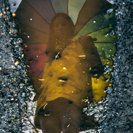 A woman's reflection in a rain puddle.