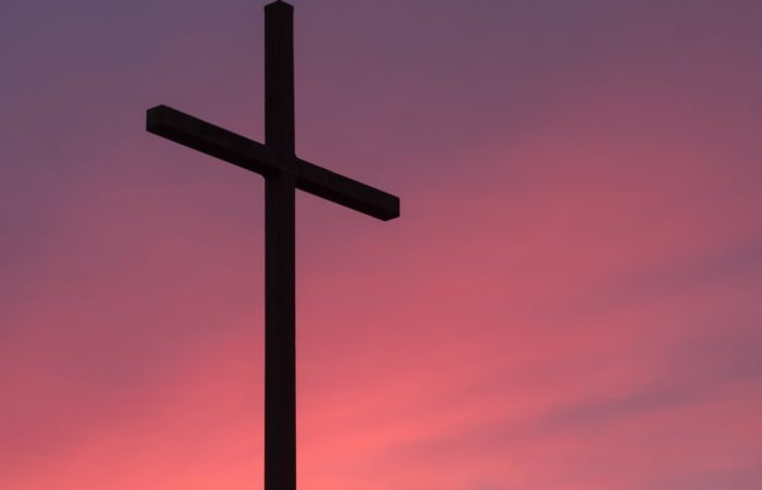 black cross in purple/pink sunset