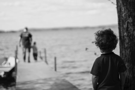 child's perspective watching an adult walking away with another child on a boardwalk