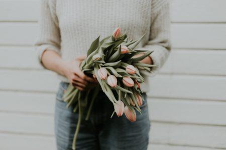 woman holding bundle of tulips