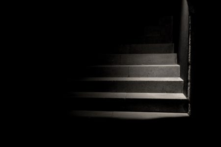 dark staircase with a light illuminating the next few steps up