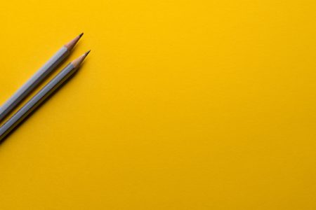 two gray pencils on yellow background
