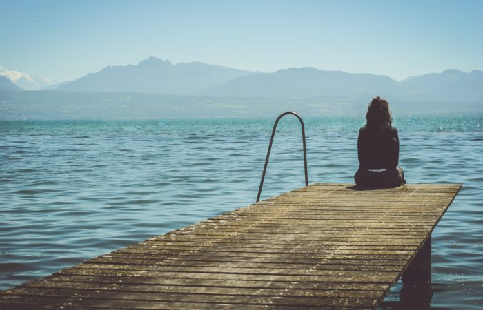 a woman sitting at the end of a dock looking at the water