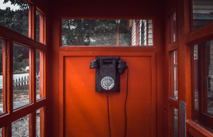 a black rotary telephone on a red wooden wall