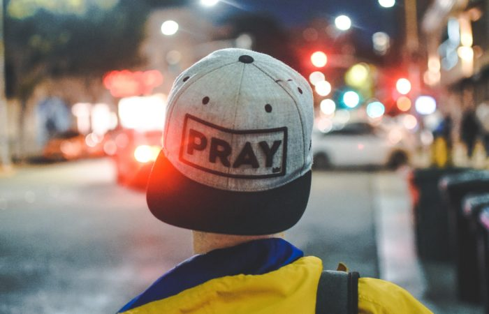"Person wearing hat that says ""Pray"" standing on busy street."